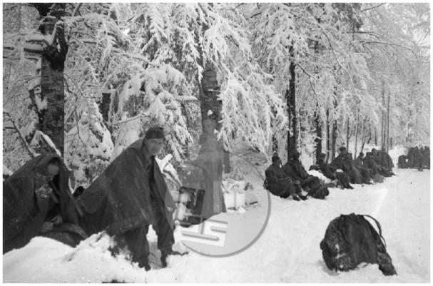 Počitek partizanov v tedaj še zasneženem Trnovskem gozdu med pohodom proti Trstu, 29. 4. 1945.