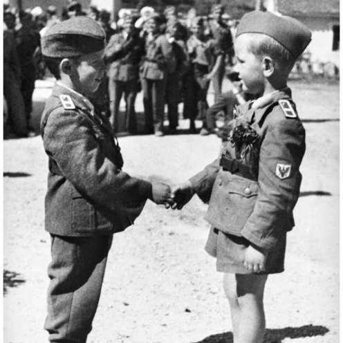 13_6744-10; Dečka pri pozdravu, oblečena v otroško izvedbo domobranske uniforme, na domobranski proslavi na Ljubljanskem gradu novembra 1944. Foto: neznan.