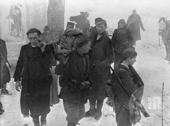 Prenos ranjencev na Paškem Kozjaku 19. februarja 1944. Prvi z leve je verski referent divizije Jože Lampret. Foto: Jože Petek