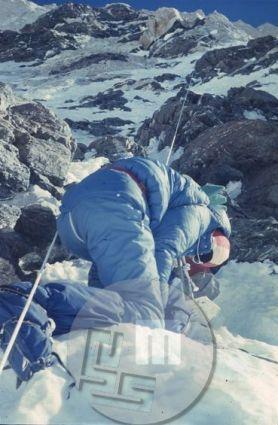 Janko Ažman si na višini 7000 m zavezuje derezo – na taki višini je z rokavicami to težko, brez njih pa nevarno početje. Ažman je bil leta 1972 v navezi z Matijo Maležičem prvi Jugoslovan, ki je prestopil višino 8000 m. Ta naveza je dosegla višino 8200 m, nato pa so morali zaradi hudega sneženja zapustiti goro. Foto: Aleš Kunaver.