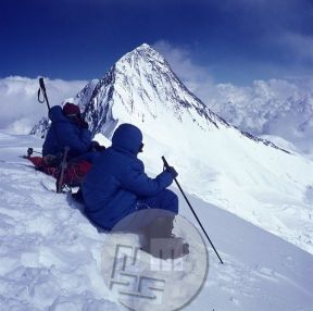 KA_4341: Zdravnik Jože Andlovic (na levi) in Lojze Golob na vrhu Anapurne IV (7524 m), zadaj vrh Anapurne II (7937 m), 21. 10.1969. Andlovic je bil prvi jugoslovanski zdravnik, ki je prišel na himalajski vrh, naslednji dan pa je v taboru III na višini okrog 6600 m – v najvišji bolnišnici na svetu z infuzijsko tekočino in drugimi zdravili oskrbel Kazimirja Drašlarja, ki se je z omrznjenimi prsti na rokah in nogah vrnil z vrha Anapurne II. Foto: Aleš Kunaver.