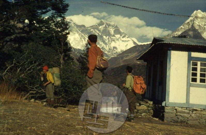 KA_747: Aleš Kunaver in novinar Zoran Jerin (v sredini) sta med oktobrom 1962 in februarjem 1963 kot prva Slovenca prepotovala vzhodni Nepal in sicer od Katmanduja do Dardžilinga, da bi opravila ogledni pohod za naslednje odprave prek zahodnega Nepala. Ko je Aleš zagledal steno Lhotseja (na posnetku v sredini, desno slavni samostan Tjangboče), ga je tako prevzela, da je postala cilj jugoslovanske odprave leta 1981. Foto: Aleš Kunaver.