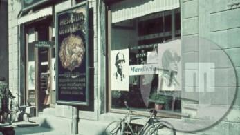 """Za proslavo priključitve Ljubljanske pokrajine k Italiji je okupator 3.5.1941 prelepil ljubljanske hiše in izložbe s slikami kralja Emanuela III. in Mussolinija. Med obema portretoma je v italijanščini napis """"Mesnica""""."""