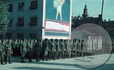 Postrojena nemška vojska pred stavbo, na kateri je reklama. Napis je zabrisan, pisalo pa je Zlatorog.