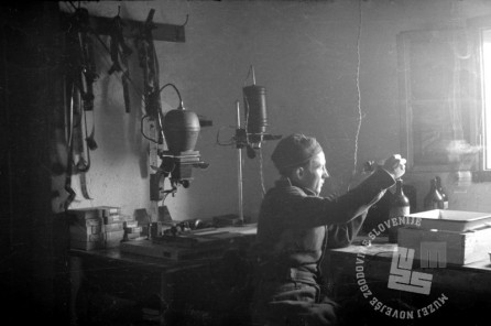 175-389_38: Franjo Veselko v temnici fotosekcije SNOS pregleduje posnetke, Črnomelj, 23. oktober 1944, foto: Maksimiljan Zupančič.