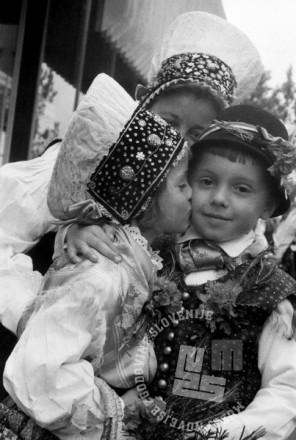 Poljubček in otroška spontanost: Otroka v narodnih nošah na Kmečki ohceti v Ljubljani. Prva Kmečka ohcet je bila leta 1966 in velja za prvo množično javno prireditev po drugi svetovni vojni, na kateri so se ljudje v javnosti lahko pokazali v narodnih nošah. Kmečka ohcet, na kateri so se poročali slovenski in tuji pari, je postala tradicionalna turistična prireditev v Ljubljani in je s kratko prekinitvijo potekala do leta 1990. Celotedensko prireditev po ljudskih šegah in običajih so spremljale folklorne in glasbene prireditve. Ljubljana, 1968. Foto: Edi Šelhaus