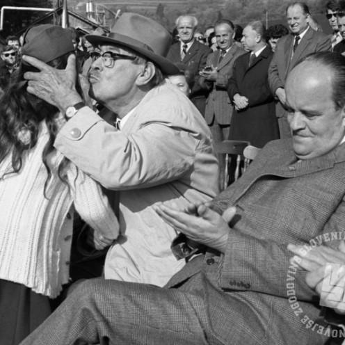 Poljub sede: Poljub pionirke, ki ga je Franc Leskošek – Luka, eden osrednjih medvojnih in povojnih komunistov, na proslavi ob odprtju Partizanske magistrale Črnomelj–Soteska podarjal kar sede. Od otrok – pionirjev se je med komunizmom pogosto pričakovalo, da izrekajo zahvale in poljubljajo politične predstavnike. Na protokolarni ravni niso veljala pravila, ki so še v prvi polovici 20. stoletja velevala: »Ne poljubljaj tujih otrok, čeprav si družini dober znanec, pa tudi svojih ne dovoli poljubljati tujemu človeku.« 29. oktober 1978. Foto: Miško Kranjec