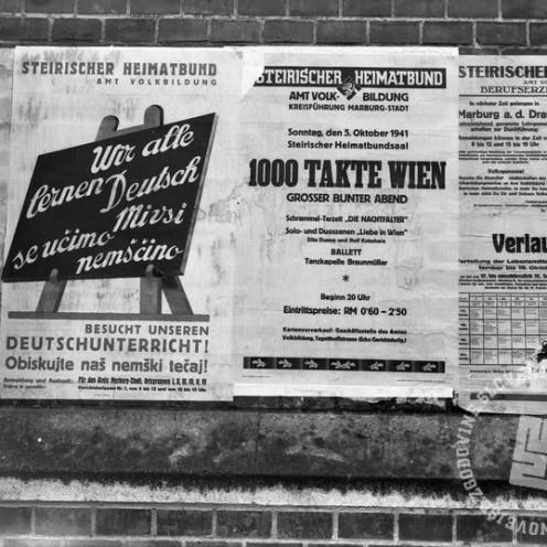 """Di267: Plakat """"Wir allen lernen Deutsch"""" izobešen v Mariboru, oktober 1941, foto Veit."""
