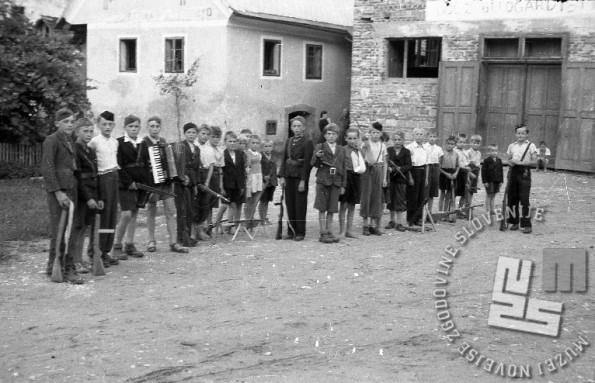 Pionirski odred v Dolenjskih Toplicah, poleti 1944. Foto: Maksimilijan Zupančič – Milijan /vse podatke naprej je posredoval g. Jože Bučar/ Na posnetku sta dve četi, poimenujmo ju leva in desna. Mali partizani so fotografirani na trgu pred nedokončanim Sokolskim domom (na desni strani posnetka). Prvi z desne je komandant desne čete Rajko Heningman, rojen 1928, deveti z desne (v ozadju) je Jože Bučar, enajsti z desne (s povito roko) pa Ladi Heningman. Komandant pionirskega odreda Jože Zupanc stoji na sredini, med borci obeh čet. V levi četi pa so: peti z leve Stojan Vajksel, harmonikaš čete, četrti z leve mogoče Jože Peršina.