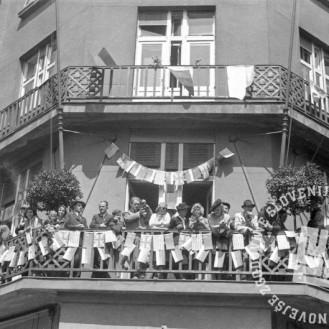 FS2169: Ljudje pozdravljajo partizane iz balkona okrašene stavbe na današnji Slovenski cesti, nasproti glavne pošte v Ljubljani, 9. maj 1945. Foto: Jože Šmuc.
