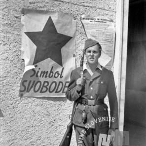 FS2201_16: Privatni posnetek, partizan pred plakatom z zvezdo in napisom »Simbol svobode« v Radovljici, 10. maj 1945. Foto: Finžgar.