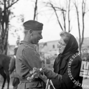 FS2246_09: Prihod partizanov v Maribor. Starejša gospa se rokuje z mladim partizanom, morda srečanje matere in sina, 10. maj 1945. Foto: Marijan Pfeifer, st.