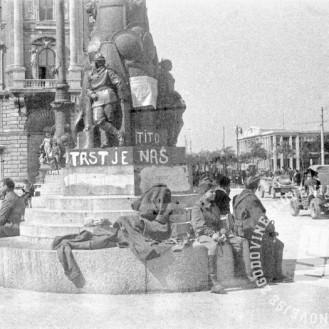 FS2156_16: Partizani na počitku ob spomeniku z napisi »Trst je naš«, »Tito«, »Smrt fašizmu« in raznimi razglasi na trgu (Piazza Unità) v Trstu, 8. maj 1945. Foto: Nande Vidmar.