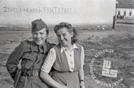 FS2023_17a: Politkomisar Mirtič Jože z Gabrijelo, v ozadju napis »Živeli hrabri partizani!«, Murska Sobota, 19. april 1945. Foto: Jože Kološa.