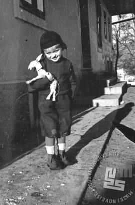 """Deček z izrezljanim osličkom iz lesa. Otroci največ časa preživijo v igri vse dokler ne pride do trenutka, ko vojno dogajanje naredi rez s preteklimi """"zlatimi časi"""". Foto: Vinko Bavec"""