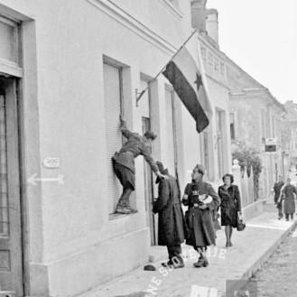 FS2108_39: Izobešanje zastave na hiši v Kočevju, 4. maj 1945. Foto: Maksimilijan Zupančič.