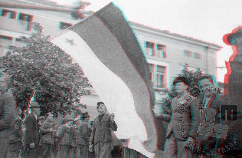 FS2126_2: Ustanovitev Narodne vlade Slovenije v Ajdovščini, 5. maj 1945. Novo vlado so sestavljale politične osebnosti iz vrst komunistov, kakor tudi iz meščanskih strank in skupine krščanskih socialistov. Na fotografiji so dečki s slovensko zastavo z zvezdo na beli podlagi. Barve na slovenski zastavi so si od spodaj navzgor sledile: rdeča, modra, bela; običajno je bila rdeča zvezda na sredini. Foto: Edi Šelhaus. The creation of the Slovene National Government in Ajdovščina, 5th May 1945. The new government was made up of political figures who were members of the Communists, the bourgeois parties and the Christian Socialists. The photo shows a group of boys carrying a Slovenian flag with the star on a white background. The colours of the Slovenian flag followed from bottom to top: red, blue, white; the red star was usually in the middle. Photo: Edi Šelhaus.