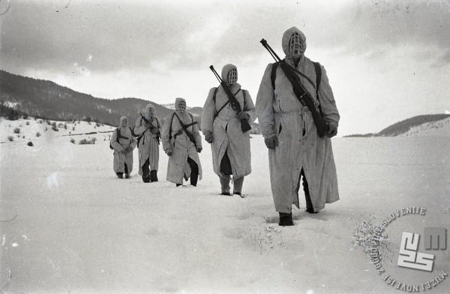 Partizanska patrulja Notranjskega odreda v belih haljah v snegu na izvidniškem pohodu v Loški dolini leta 1945. Foto: Edi Šelhaus
