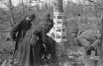 Borci 1. bataljona Ljubljanske brigade si ogledujejo fotografije potujoče fotografske razstave z domačih in tujih bojišč 25. marca 1945. Foto: Milan Štok