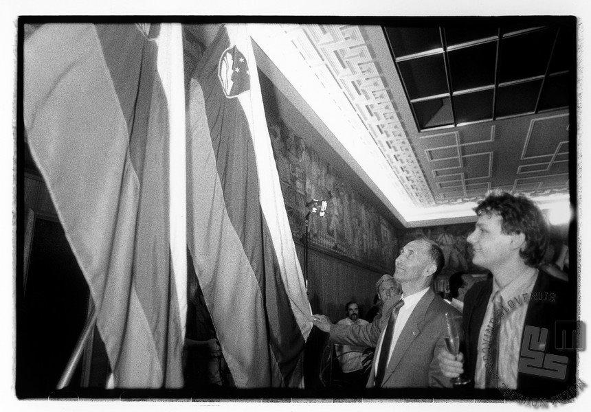 Ivan Oman (levo) in Marjan Podobnik si ogledujeta »novo« državno zastavo, ki je bila s 100. amandmajem k slovenski ustavi določena dan prej, Ljubljana, 25. 6. 1991. Foto: Tone Stojko