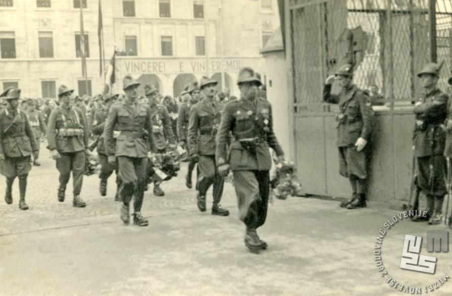 Vrnitev enainsedemdesetih (od okoli šeststotih) preživelih vojakov smučarskega bataljona Monte Cervino pred vojašnico Testafochi. Virgilij Tavčar je drugi z leve s šopkom cvetja. Sprejem in mimohod v Aosti, 20. 4. 1943 (izvirnik hrani Virgilij Tavčar).