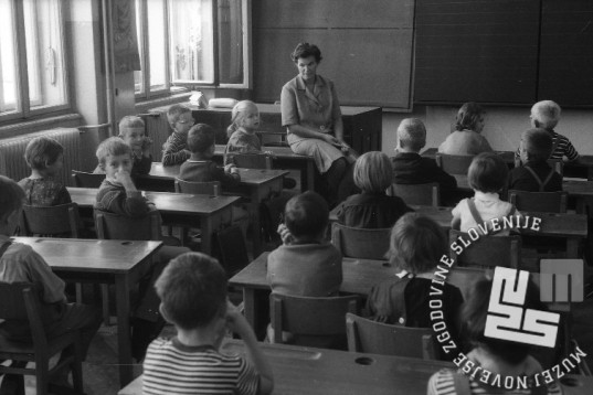 8. septembra 1964 so učenci 1. razred OŠ Frana Levstika v Ljubljani pazljivo poslušali razlago učiteljice. Foto: marjan Ciglič