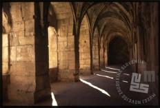 Križni hodnik viteškega gradu Krak des Chevaliers, poznan tudi kot kurdska utrdba, zaradi kurdske garnizije, ki jo je v 10. stoletju tam naselil emir. V 11. stoletju so grad dobili v roke križarji in je dolgo časa ostal nepremagljiva križarska utrdba. Šele v 13. stoletju so ga zavzeli Mameluki. Po koncu križarskih vojn je utrdba izgubila svoj pomen in so jo začeli naseljevati kmetje. Leta 2006 je bila vpisana na seznam UNESCOove svetovne dediščine. / Cloister of the Knights castle Krak des Chevaliers, also known as the Kurdish stronghold, because of the Kurdish garrison, which was settled there in the 10th century by the emir. In the 11th century the castle got into the hands of the Crusaders and has long remained an impregnable Crusade fortress. It was only in the 13th century when it was taken by Mameluks. At the end of the Crusades the fort lost its importance and began to be settled by the farmers. In 2006, it was inscribed on the UNESCO List of World Heritage.