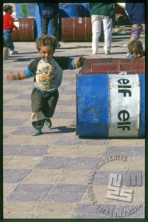 Otrok v igri med bencinskimi sodi na otoku Arwad. / A child playing between gasoline barrels on the Arwad Island.