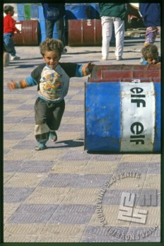 Otrok v igri med bencinskimi sodi na otoku Arwad. / A child playing between gasoline barrels on the Arwad Island.