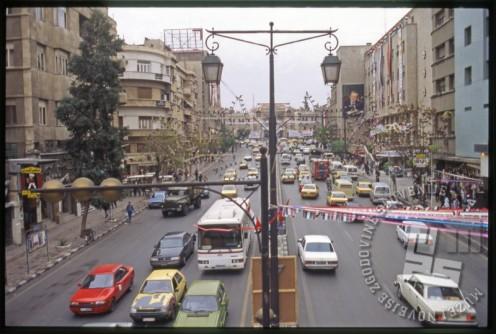 Ulica v Damasku. Na desni strani fotografije je zidna poslikava portreta Hafeza al Asada, predsednika Sirije med 1971 in 2000, očeta Bašar al Asada. / A street in Damascus. On the right side of the photo, a wall painting portraits Hafez al-Assad, the president of Syria between 1971 and 2000, the father of Bashar al-Assad.