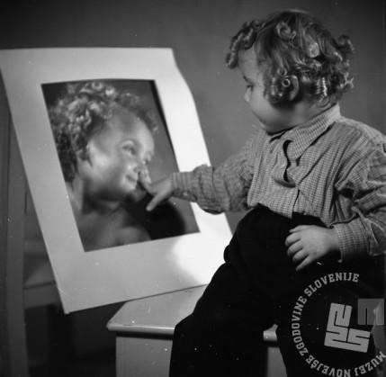 BŠ492_3: Hči Jana si ogleduje svoj fotografijo. Med leti 1949 in 1951.