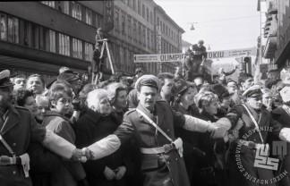 Množico zadržujejo policaji, da ne bi ovirali sprevod svatov, ki so šli po nekdanji Titovi (danes Slovenski) ulici (pri Cankarjevi ulici in Nami), 8.3.1966. Foto: Marjan Ciglič