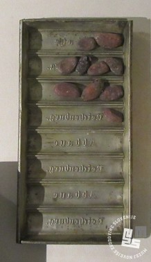 Kalup za čokolado z napisom Abbaye Reichenburg in kakavova zrna. Hrani: MNZS.