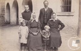 Pater Angel Pečnik z očetom, mamo in nečaki, slikan pri stavbi za gojence, okrog leta 1915. Foto: neznan, hrani MNZS.