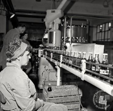 Cockta je večkrat spremenila ime. Sprva je bila Jugocola, nato Yugo Cockta, oglaševala pa se je kot Cockta Cockta. Polnjenje Yogocockte v podjetju Slovenijavino, Ljubljana, 9. 8. 1966. Foto: Marjan Ciglič, hrani Muzej novejše zgodovine Slovenije.