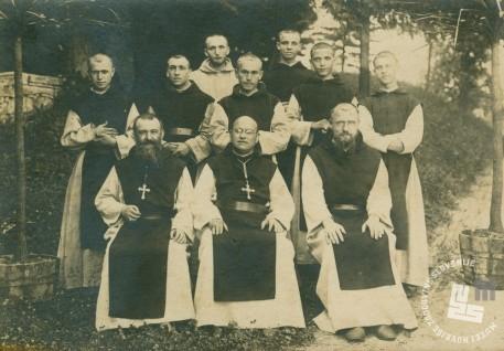Prvi z desne sedi p. Rafael Grzina. Je v družbi z opatoma in menihi, okrog leta 1927. Foto: neznan, hrani: MNZS.