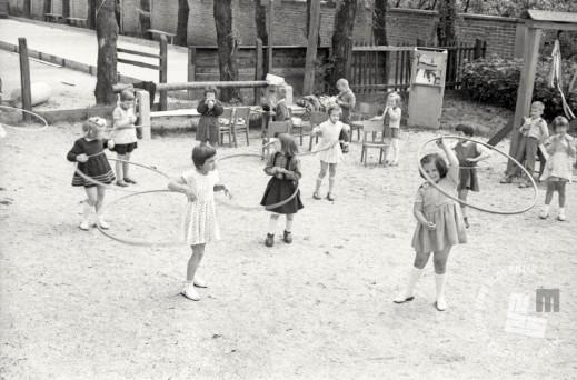 DE513_1: Otroci poskušajo obroč čim dlje obdržati na bokih, 1959. Foto: Edi Šelhaus, hrani: MNZS.