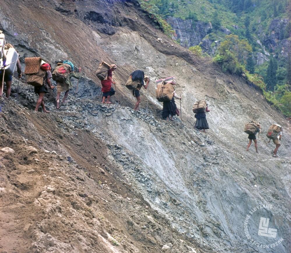 Med 3. jugoslovansko himalajsko odpravo na Anapurno: nosači, med njimi tudi ženske, so težke tovore, tudi po strmih in nevarnih terenih, večinoma prenašali bosi, Nepal, 1969. Barvni diapozitiv, 6 x 6 cm, inv. št.: KA1101. Foto: Aleš Kunaver.