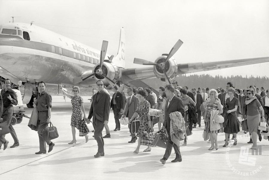 Letalo DC-6B in potniki na Letališču Brnik, julij 1964. Foto: Svetozar Busić.