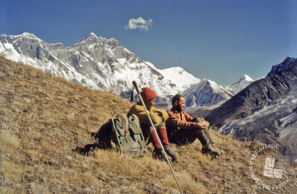 Novinar Zoran Jerin (desno) s Šerpo Pembo Tenzingom, v ozadju trije od petih najvišjih vrhov sveta: v sredini Lhotse, na levi konica Mt. Everesta, ki kuka izza grebena Nuptseja, na desni piramida Makaluja, Nepal, 16. december 1962. Barvni diapozitiv, leica, inv. št.: KA1279. Foto: Aleš Kunaver.