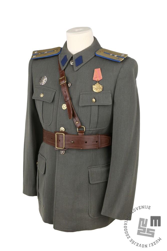 Bluza navadne uniforme za postroj po pravilu iz leta 1946 z epoletuškami kapetana iz let 1951 -1953. »Zaprto modra« barva rombov in egalizira epoletušk je bila predpisana za enote Korpusa narodne obrambe Jugoslavije – KNOJ-a. Bluzo hrani Muzej novejše zgodovine Slovenije