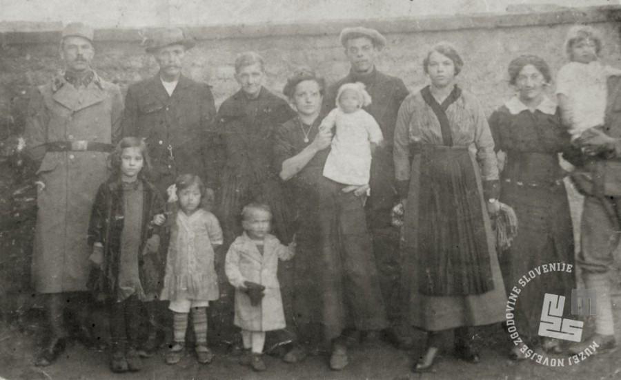 Tri generacije družine Vuga v Brucku na Litvi. V sredini je Hortenzija Vuga, ki drži v naročju Julijano (Julico), za krilo jo drži mali Franc. Levo od Hortenzije sta stara starša Vuga, okoli njiju pa njuni otroci. Manjka sin Franc (Hortenzijin mož), ki je bil na soški fronti. Foto: A. Tonke, begunsko taborišče Bruk na Litvi; hrani: družina Vuga.