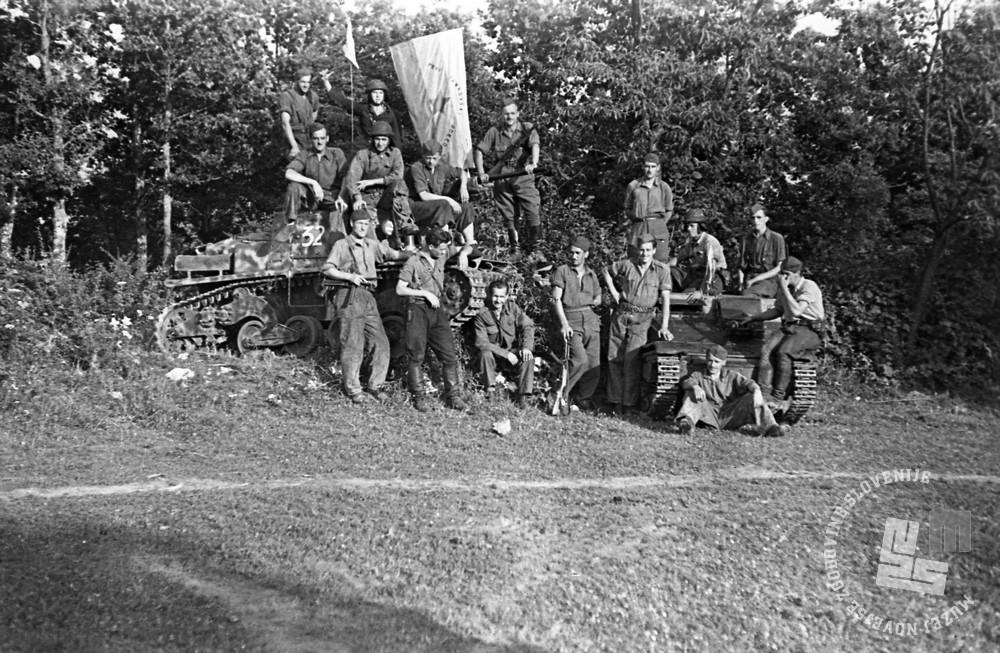 Borci 1. tankovskega odreda s svojo novo zastavo ter italijanskim tankom L6/40 (levo) in tanketo CV 33.  Fotografija je posneta pri Vrčicah nad Semičem avgusta ali septembra 1944. (Muzej novejše zgodovine Slovenije, foto: Alfred Kos).