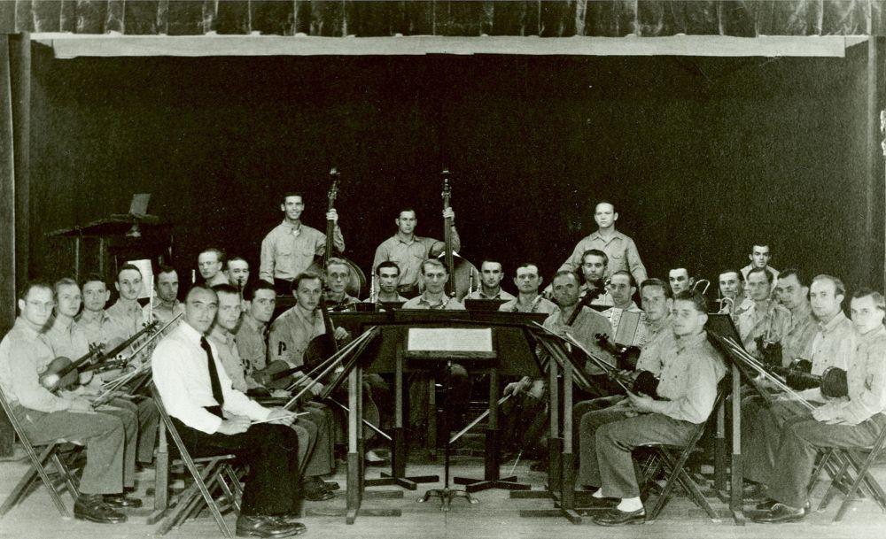 F6: Orkester Nicomei, Leopold je violonist v prvi vrsti z belimi nogavicami, Camp Roswell, 1944. (Original hrani družina Gošnik)