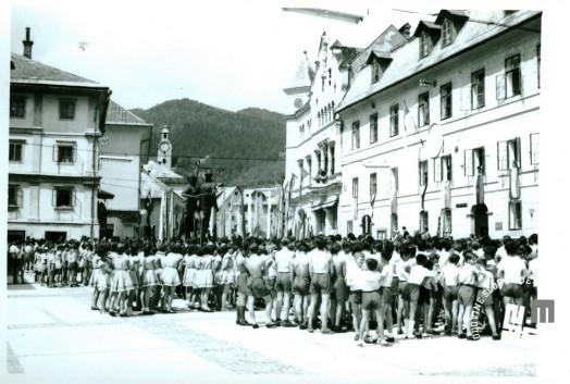 Telovadna prireditev v Idriji leta 1955. Telovadci zbrani na Mestnem trgu, kjer je bil 29. oktobra 1953 postavljen spomenik borca-rudarja in figura ženske. Foto: neznan, hrani MNZS.