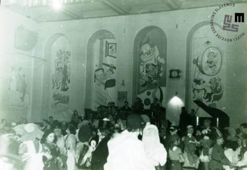 Otroška maškarada leta 1956, ki so jo organizirali člani TVD Partizan Ljubljana Narodni dom v dvorani doma. Otroci našemljeni v različne pustne maske. V ozadju vidne karikature. Foto: neznan.