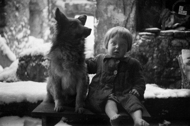 Mala Marica iz požgane vasi Papeži na Kočevskem, rojena v taborišču na Rabu, na ruševinah svojega doma, s psičkom, ki je na zapuščenem domu kot po čudežu ostal živ, 1944/1945.
