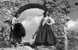 Tatjana in Zorka Legiša iz Devina ob ruševinah starega devinskega gradu, april 1946. V narodni noši sta se oblekli po nasvetu njune mame, ki je želela, da bi fotografije vsem sporočale, da v Devinu živijo Slovenci. Šelhaus je prizor posnel s fotoaparatom in s kamero Kinamo in to je bila ena od njegovih prvih filmskih reportaž na Tržaškem. Za te posnetke so ga prosili tudi na uredništvu časopisa Primorski dnevnik, v katerem je bila ena od fotografij iz serije tudi objavljena.